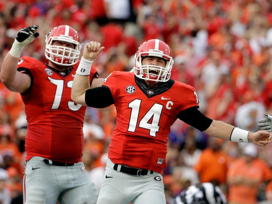 Georgia quarterback Hutson Mason, right, celebrates after running the ball to score a touchdown in the first half of an NCAA college football game against Clemson, Saturday, Aug. 30, 2014, in Athens, Ga. (AP Photo/David Goldman)