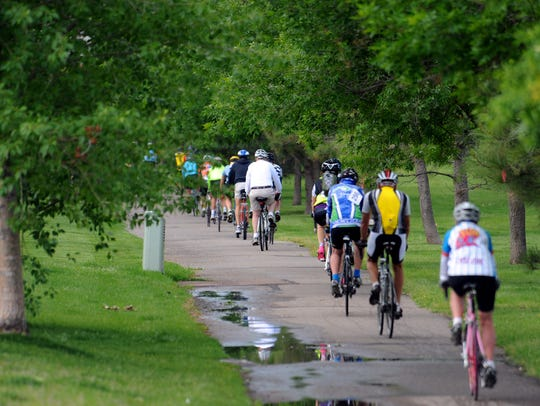 Bicyclists pedal down the River's Edge Trail.