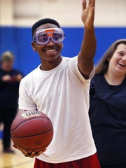 Shortridge High School student Chris Munday, wearing a Concussion Goggle that simulates blurred vision resulting from a concussion, tries to make a basketball shot in the school's gym as the Dave Duerson Athletic Safety Fund non-profit organization came to the school at 3401 N. Meridian, Indianapolis, on Monday, Oct. 26, 2015 to heighten concussion awareness among youth. Kathy Langdon, the school's athletic director and also health and wellness facilitator at Indianapolis Public Schools, directed students in several exercises demonstrating how the goggles work. The program is intended to educate all students, not just athletes. The organization has donated more than 60 goggles for the educational program. Michael Duerson, Muncie, father of former Chicago Bear Dave Duerson, who committed suicide after suffering numerous concussions, was at the school on Monday to promote the group's efforts.