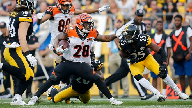 Cincinnati Bengals running back Joe Mixon (28) fights off tackles on a carry in the second quarter of the NFL Week 7 game between the Pittsburgh Steelers and the Cincinnati Bengals at Heinz Field in Pittsburgh on Sunday, Oct. 22, 2017.