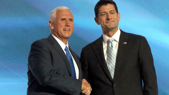 Republican vice presidential nominee Mike Pence (left) is welcomed to the stage by House Speaker Paul Ryan at the GOP National Convention in Cleveland, Ohio on July 20, 2016.