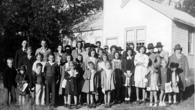The Rev. Herbert S. Turner at left in the back row, stands outside of Pines Chapel around 1944. This is the church that was rolled across the road and connected to an old one-room school house.