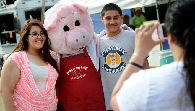 Gracie Morris, left, and Nick Adkins pose for a photo with the Pork in the Park Pig.