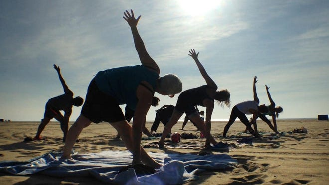 Patrons take advantage of free yoga on the beach by Carmel Calcagno, owner of Yoga Anjali in Belmar.