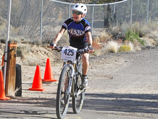 Wiley Corra, of Durango, Colo., crosses the finish line in first place during the Road Apple Rally's 15-mile route on Oct. 4, 2014, at Lions Wilderness Park in Farmington.