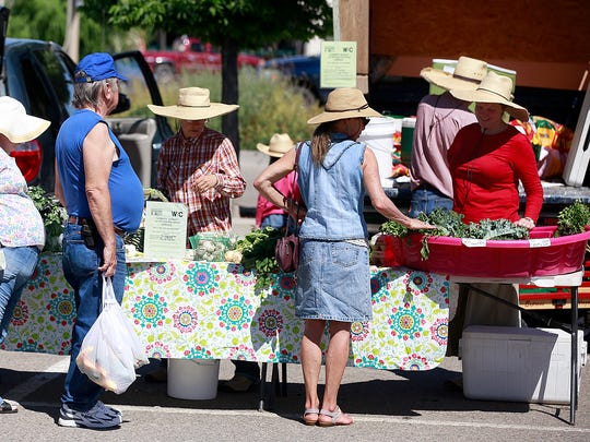 Customers line up at Bridgewater Produce during the Farmington Growers Market on Saturday at the Farmington Museum at Gateway Park.