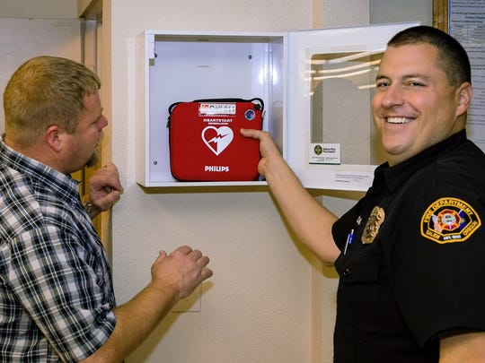 Shelter manager Adam Lehman and Salem Fire Dept. EMS Trainer Willy Giddings install an AED at the Salvation Army Lighthouse Shelter in Salem, Ore.
