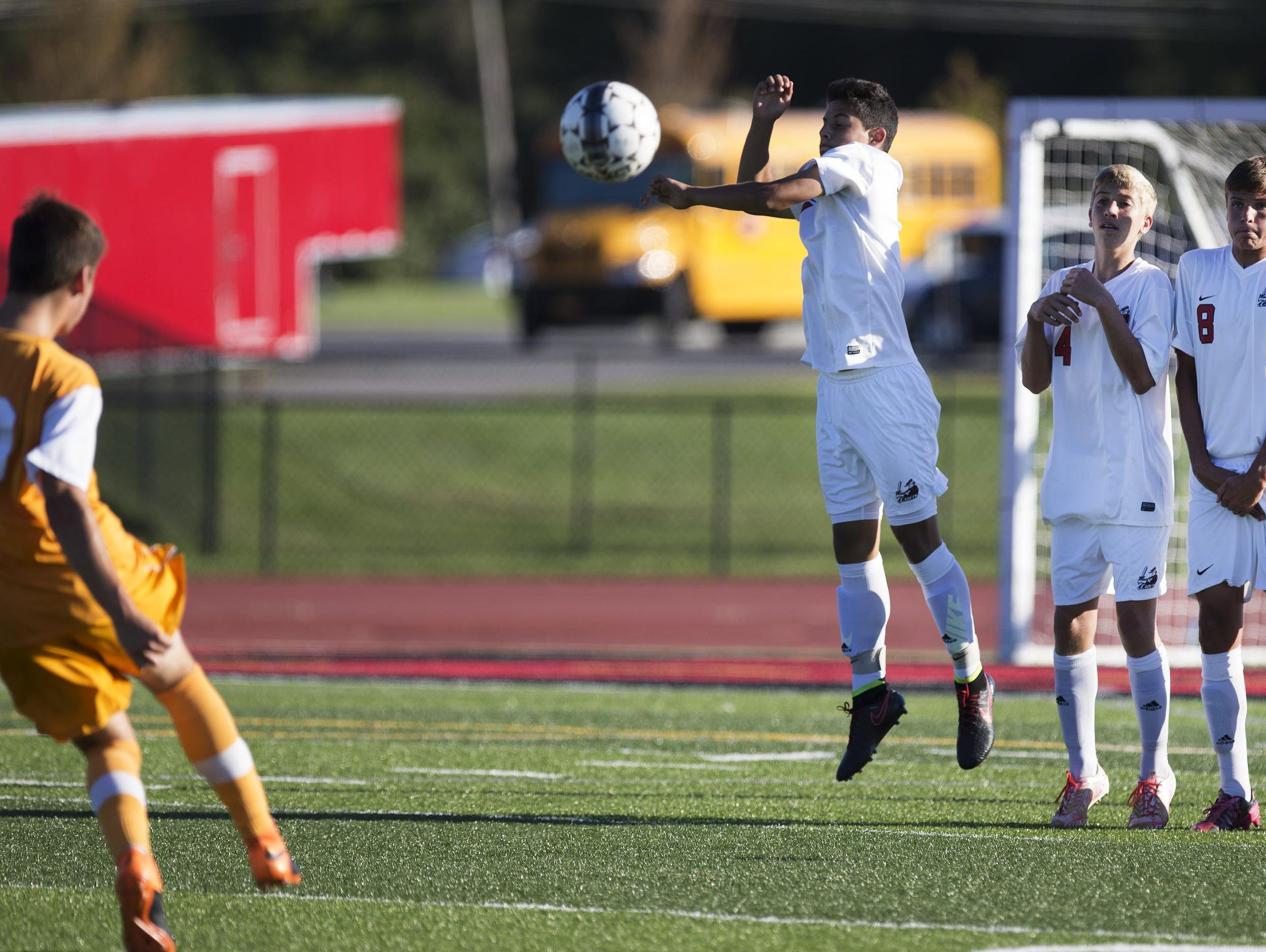 Hilton's Noah Malta, Brian Wilkin, and Brady Farrell stand in front of the goal as Churchville-Chili's Lukas Fernandes attempts a penalty kick during a game at Hilton High School on Wednesday, September 23, 2015.