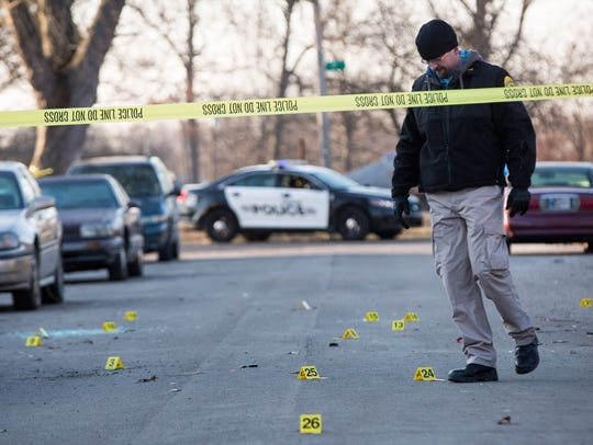 Police investigators look over the scene of a fatal