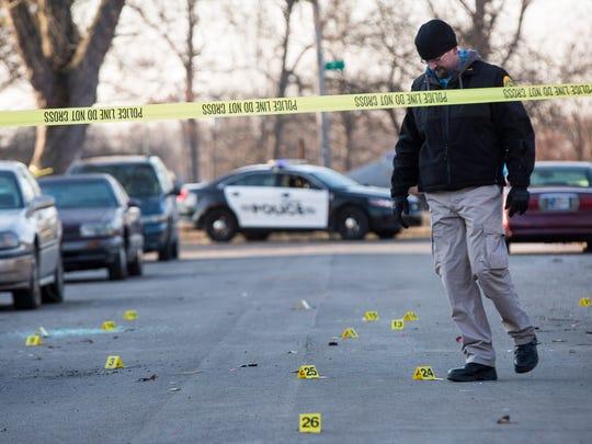 Police investigators look over the scene of a fatal