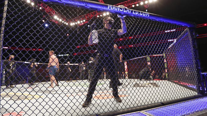 A worker wipes down the octagon between bouts during UFC 249 in Jacksonville, Fla.