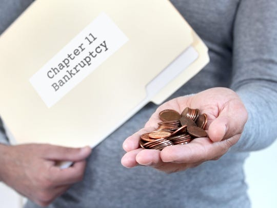 A man holds a manila folder marked Chapter 11 Bankruptcy, offering a handful of pennies in his other hand.