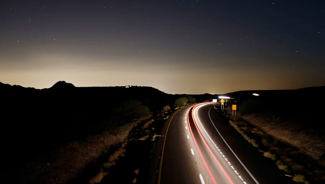 Taillights streak down Interstate 17 on a recent moonless night south of Black Canyon City. The southern horizon is illuminated with light from the metro Phoenix area.