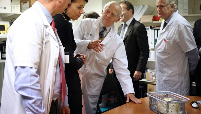 French Social Affairs and Health Minister Marisol Touraine, second left, listens to French leading heart transplant specialist Alain Carpentier, third left, at Georges Pompidou European hospital in Paris, on Dec. 21, 2013.