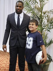 DeMarco Murray, Rochester Press-Radio Club Sports Personality of the Year, left, poses with Domenic Mancuso, 10, of Penfield before the beginning of the annual dinner.