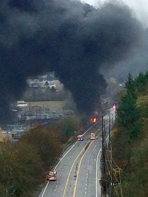 In this photo provided by the Portland Police Bureau, plumes of black smoke fill the sky after a semitrailer truck crashed on a roadway near a Portland, Ore., railroad yard Sunday, Dec. 13, 2015. The truck driver was killed, Portland police said. Portland Fire spokesman Terry Foster said the fire happened when the truck, carrying some sort of fuel product, crashed, causing fuel to leak underneath the parked train cars.