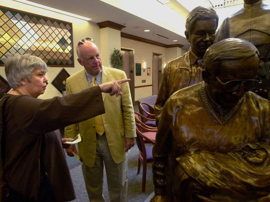 "Wisconsin Artist Gwendolyn Gillen views her sculpture, ""Tradition of Caring,"" with John Burke of Milwaukee in 2003.  The ""Tradition of Caring"" scupture was a gift presented to Columbia St. Mary's Ozuakee Campus by the Doerr family."