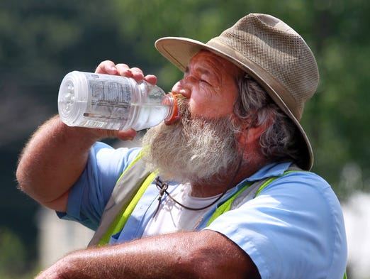 Buck LaBare, of Len Riegler Blacktop, cools off with a drink of water as he works laying asphalt on Saddlebrook Drive, Florence.  The asphalt is 300 degrees; the air where the crew was working is about 180 degrees, according to foreman Jack LaBare.