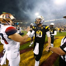 Taylor Kelly greets Arizona linebacker Jake Fischer prior to the 87th Territorial Cup on Nov. 30, 2013, in Tempe.