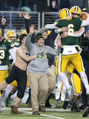 St. Edward's head coach Tom Lombardo celebrates with his team after their D1 state championship game victory against Colerain in Tom Benson Hall of Fame Stadium in Canton on Friday, Nov. 30, 2018.