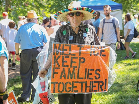 Berta Lambert hands out buttons to protesters at the Families Belong Together March at Washington Park in Over-The-Rhine, Cincinnati, on Saturday, June 30, 2018.