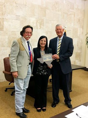Bernie Sargent, left, presented the Texas Treasure Business Award to Kemp Smith's Michele Miller and Michael D. McQueen.