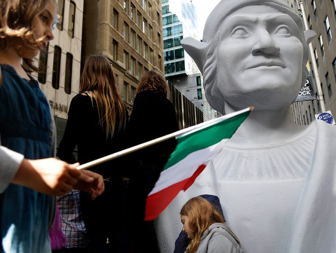 Isabella Nordstrom, left, waves an Italian flag while her cousin, Abigail, rests on a large bust of Christopher Columbus before the start of the Columbus Day Parade on Oct. 14 in New York City. The parade has been held every year since 1929.