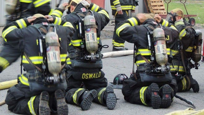 In this undated photo, firefighters with the Roosevelt Fire District are seen wearing self-contained breathing apparatus. The district received a federal grant to replace its 13-year-old air packs.