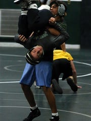 South Plainfield High School wrestling team as it trains inside the school's wrestling room ,113-pounder Jake Giordano is held up side down by a team mate as he works out along the rest of the team on Thursday December 17, 2015.