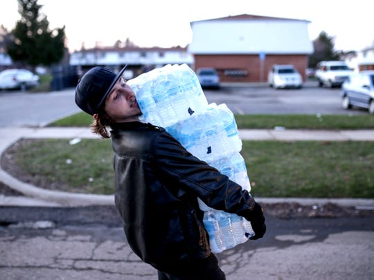 Flint resident Christopher Kabel carries multiple cases of bottled water to help hand out to residents at River Park Apartments in Flint on Monday April 4, 2016. Kabel helped a group of students from University of Illinois at Chicago who traveled with Chicago resident William Hall to deliver books to the children dealing with the Flint water crisis and water to their families at a couple locations around the city.