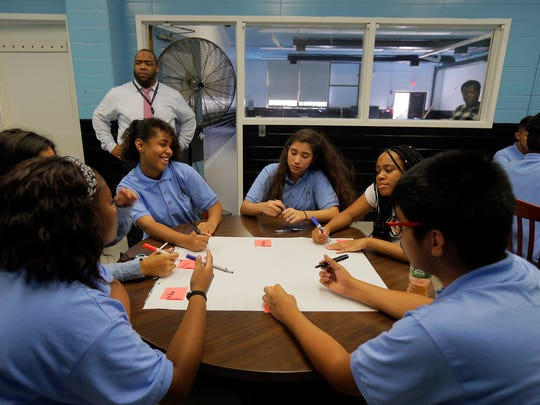 De'Jia Dawkins, 14, writes an adjective to describe herself during an ice breaker exercise with Dream Academy students on the first day of school at Asbury High School in Asbury Park, NJ Thursday September 8, 2016.