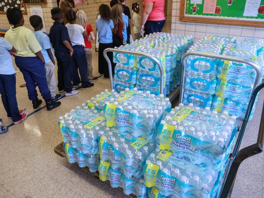 Freeman Elementary School students line up to go back to class past cases of bottle water donated to their school on Thursday October 8, 2015 at the Flint school.