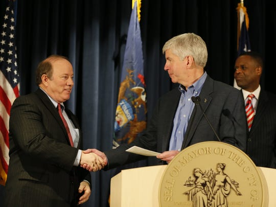 Detroit Mayor Mike Duggan, left, accepts a check from Michigan Governor Rick Snyder, as outgoing Detroit emergency manager Kevyn Orr, back right, watches during Press conference to announce the City of Detroit's exit from bankruptcy at the Public Safety Headquarters in Detroit on Wednesday, December 10, 2014.