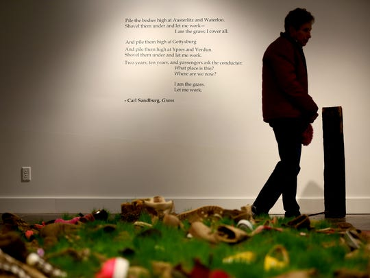 "Jo Hockenhull, an artist and volunteer with the Salem Art Association Annex, views the ""Combat Grass"" installation by Matthew Boulay and poem ""Grass"" by WWI veteran Carl Sandburg at the Salem Art Association in Salem."