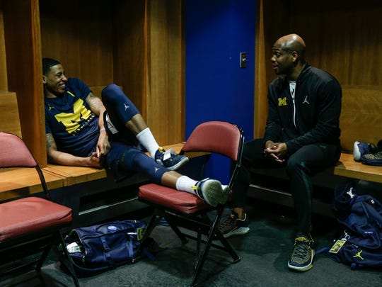 Michigan guard Charles Matthews, left, talks to assistant coach DeAndre Haynes in locker room at INTRUST Bank Arena in Wichita, Kan., Friday, March 16, 2018.