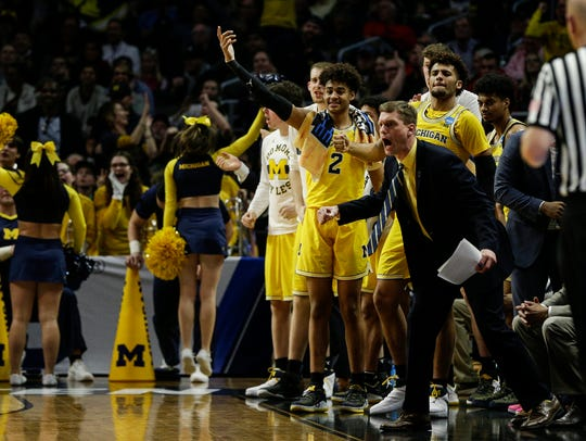 Michigan bench celebrates a play during the first half
