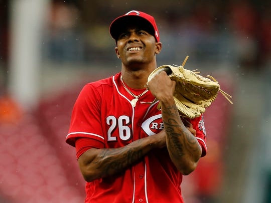 Cincinnati Reds relief pitcher Raisel Iglesias (26) hols his left arm as he returns to the dugout after the top of the ninth inning of the MLB National League game between the Cincinnati Reds and the New York Mets at Great American Ball Park in downtown Cincinnati on Wednesday, May 9, 2018. The Reds won 2-1 on a 10th inning walk off home run by Adam Duvall.