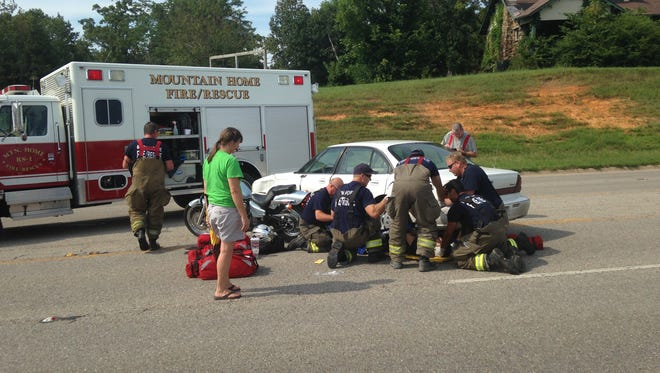 Emergency personnel treat the driver of a motorcycle injured in a crash on U.S. Highway 62 West near Bridge Baptist Church on Monday afternoon.