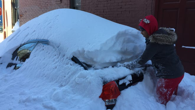 Nine Rascoe, of York, begins the process of excavating her car Sunday.