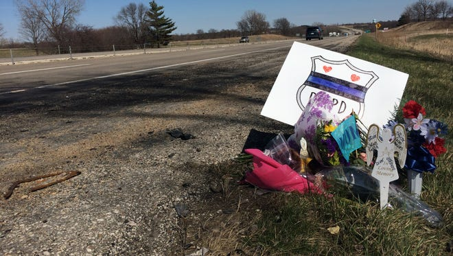 A memorial marks the spot of  Saturday's fiery Interstate 80 crash that killed four people, including two Des Moines police officers.