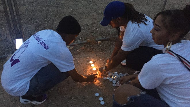 Dozens of friends of Jasmine Dunbar hold a vigil Friday evening outside the Phoenix field where police believe they have recovered her body.