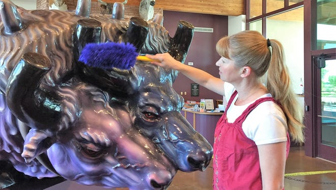 """Holly Radke, the New Mexico Farm & Ranch Heritage Museum's collections manager, dusts off the oxen on the front end of the 22-feet-long """"Sodbuster, San Isidro"""" sculpture by the late artist, Luis Jiménez. The artwork will be presented at a free reception from 5 p.m. to 7 p.m., May 18."""