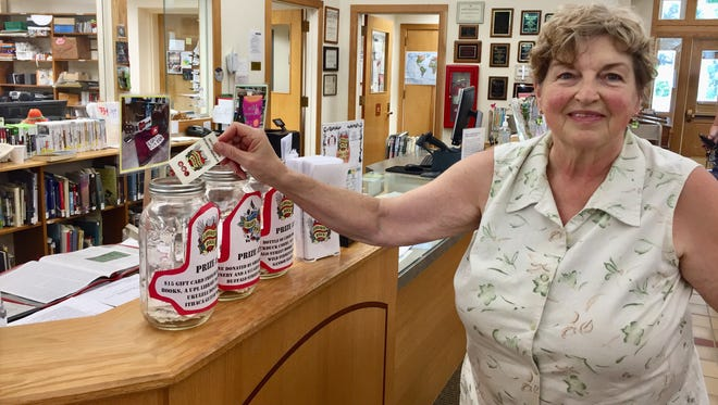 Patricia Heckart, a participant in the adult summer reading program, Libraries Rock, drops her punch card in the jar for a prize she hopes to win at the Ulysses Philomathic Library in Trumansburg.