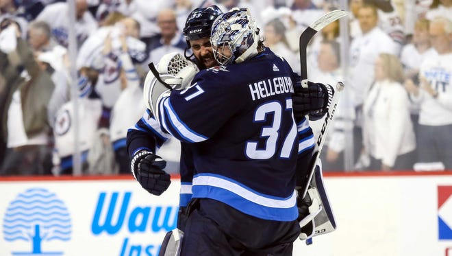 Winnipeg Jets goalie Connor Hellebuyck (37) and defenseman Dustin Byfuglien congratulate each other after a win in the playoffs.