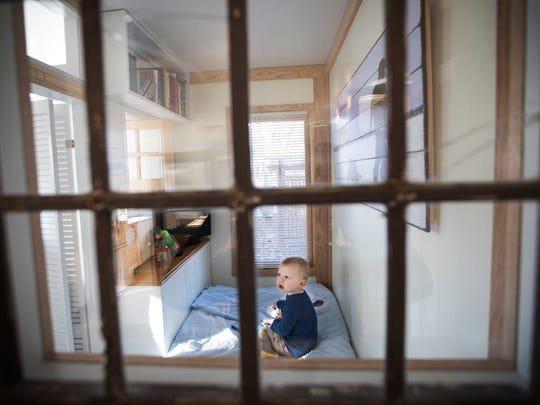 Matthew Mikkelson, 2, plays in his tiny room, seen through an antique window salvaged for the room.