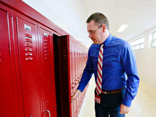 Principal Jared Wastler opens an empty narrow locker