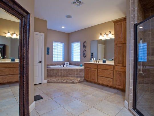 A roomy master bath featuring a garden tub, glass shower
