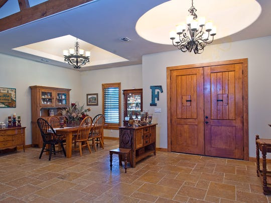 Custom Made Front Doors lead into the wide open travertine tile floored large open living space