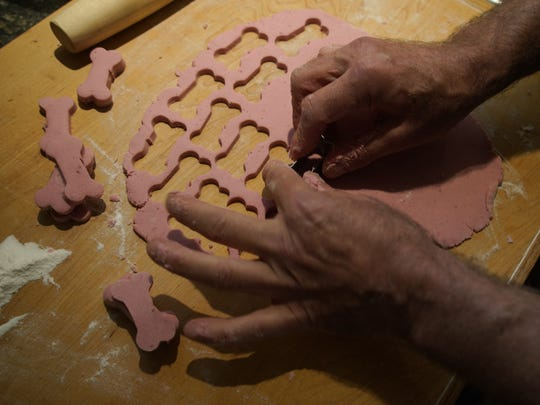 Dan Lavin, owner of Junior's Pet Food, makes bone-shaped cutouts from one of his fresh food recipes to make dog treats.