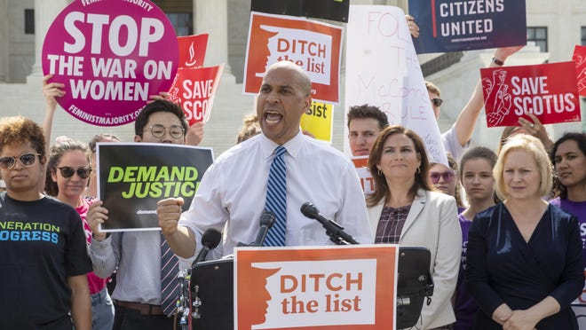 Sen. Cory Booker, D-N.J., joined at right by Ilyse Hogue, president of NARAL Pro-Choice America, and Sen. Kirsten Gillibrand, D-N.Y., speaks as he and activists demonstrate at the Supreme Court as President Donald Trump prepares to choose a replacement for Justice Anthony Kennedy, on Capitol Hill in Washington, Thursday, June 28, 2018. (AP Photo/J. Scott Applewhite)